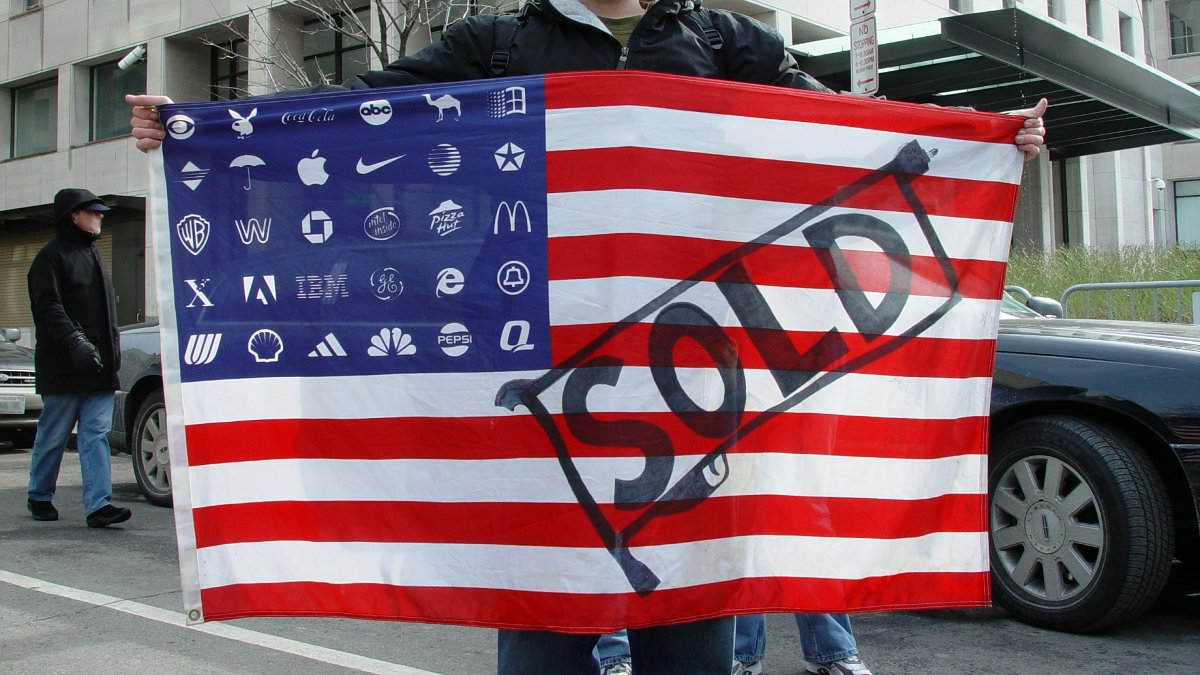Title: Protestor holding Adbuster's American corporate flag | Author: Jonathan McIntosh | Source: Wikimedia | License: CC BY 2.0